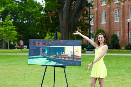 Pictured is a woman in a bright yellow dress standing next to a painting she made which resembles a corner diner in New York City. Her arms are outstretched towards the painting and she has a wide smile on her face