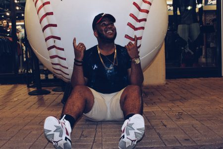 Pictured is a man sitting right in front of a giant display baseball. He has a smile on his face, is pointing up with both hands, and has his head titled upwards