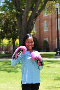 Pictured in the foreground is a woman wearing pink boxing gloves smiling towards the camera