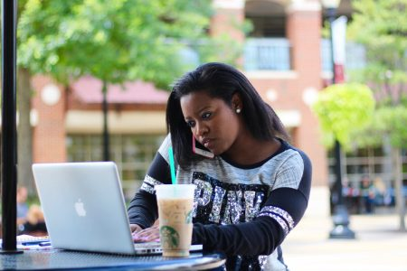 Pictured is a woman sitting down outside of the Ferguson Center on her Mac laptop with her iPhone in hand