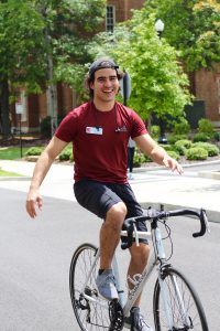 Pictured is a man on a white bicycle using no hands, he is wearing a backwards hat, a red shirt and black shorts. He has a big smile on his face.
