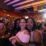 A group of five women smile into the camera with the Welcome Back Concert in the Foreground