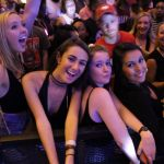 A group of four girls smile at the camera leaning over a barrier at the Welcome Back Concert