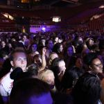 A picture of a crowd partially lit by lights from the stage. The crowd is in Coleman Coliseum and most faces are not able to be seen.