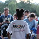 Pictured is a UP Staff member from the back facing a crowd of students. She is wearing a white Week of Welcome shirt.