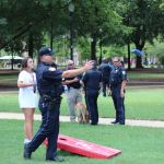 A police officer throws a bean bag in the direction of a corn hole on the quad. In the background is a female student flanked by a group of three police officers