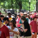 A crowd of students line up on the quad. It is a bright sunny day and most of them are on their phones
