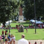 Pictured is University President Bell from his back-side. In front of him is Denny Chimes and a group of students