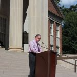 Pictured is Dr. Grady standing in front of a podium on the steps of the Gorgas Library