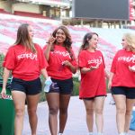 """Pictured is four female students walking into Bryant Denny Stadium all wearing shirts that read """"Script A"""""""
