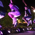 A group of students is pictured mid-jump on the ONYX stage. They are lit with purple lights and are all wearing dark clothing